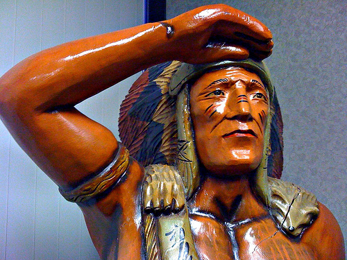 A photograph of a wood carving of an American Indian chief who appears to be searching the horizon for something