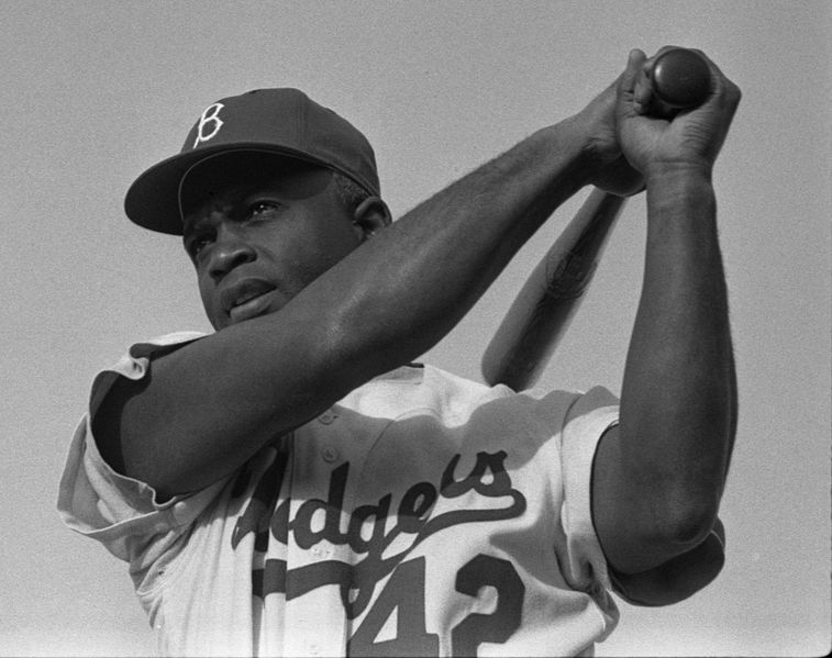 A photograph of Jackie Robinson swinging a bat in Dodgers uniform, 1954.