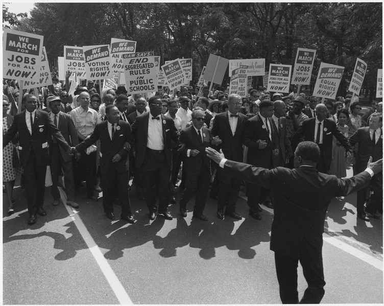 A photograph of a civil rights march on Washington D.C. in 1963; Several prominent leaders are leading them including Dr. Martin Luther King Jr.
