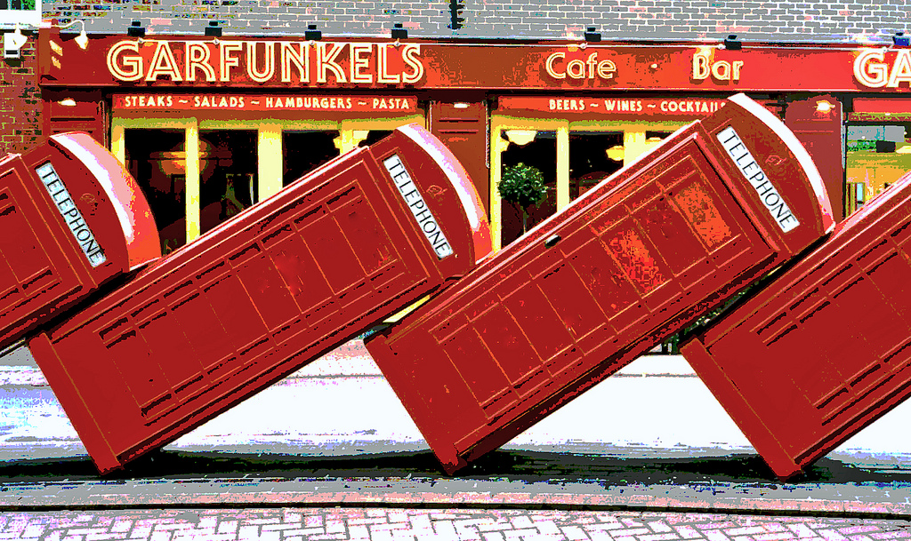 photo of four red, old-fashioned phone booth leaning against each other like fallen dominos