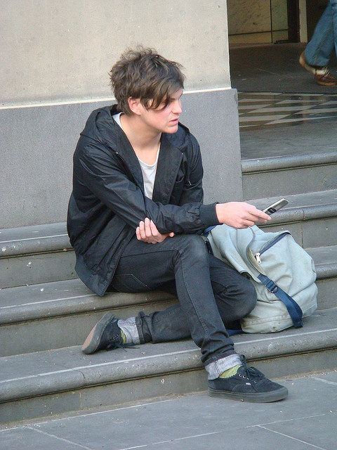 A young man sits on steps and holds a phone, but seems to be thinking
