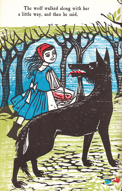 illustration of little Red Riding Hood meeting a big brown wolf with a big red tongue and teeth