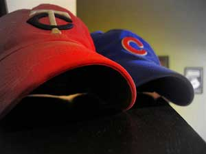 A photograph of two baseball caps on a table or shelf