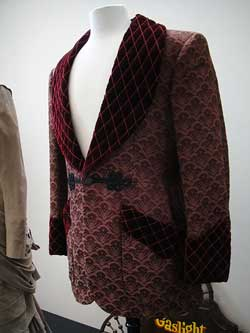 photo of a burgundy smoking jacket displayed on a partial mannequin