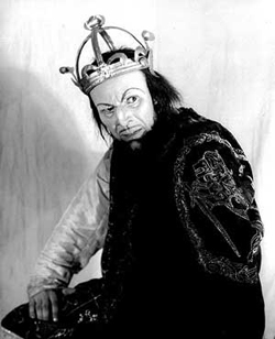 A photograph portrait of an actor dressed as MacBeth. He is wearing a crown and particularly evil looking.