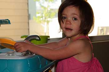 A photograph of a four or five year old girl playing with a toy kitchen set