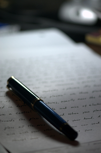 A photograph of a pen laying on a sheet of paper with hand writing on it.