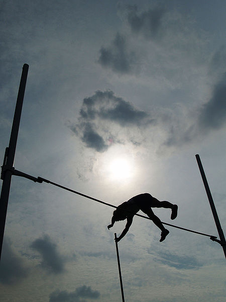 A photograph of a male pole vaulter going over the bar