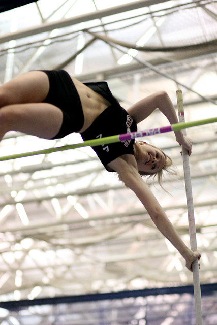 A photograph of a female pole vaulter clearing the bar