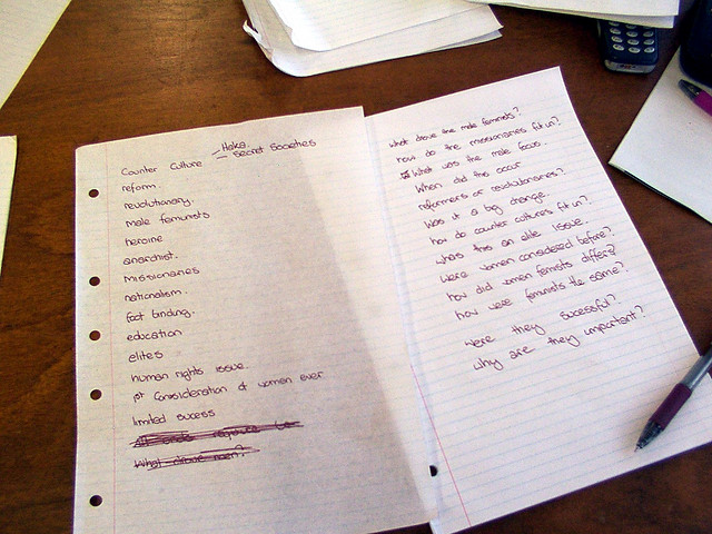 A photograph of a two sheets of lined notebook paper lying on a desk. The papers have wiring on them and a pen lying beside them.