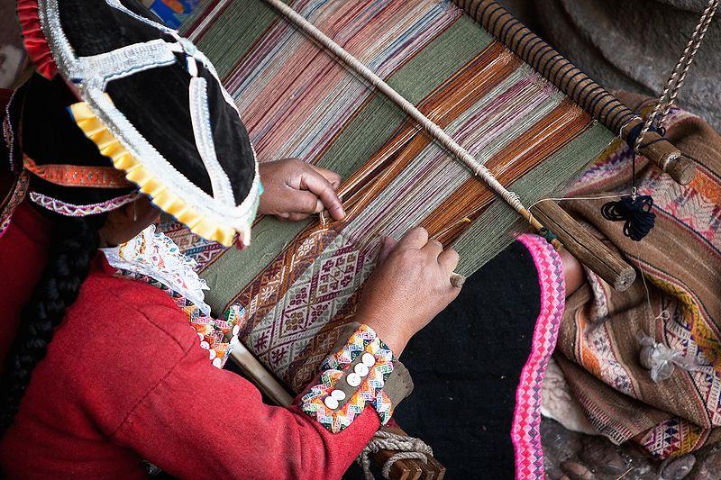 A photograph of an Inca woman weaving textiles at a manual loom.