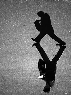 A photograph of a man walking with a notebook in his hand. His shadow appears next to him on the ground.