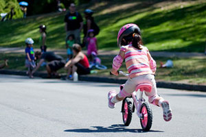 A photograph of a little girl riding away on a bike