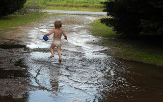A photograph of a toddler splashing through her feet in puddles