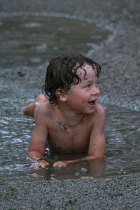 A photograph of a young boy playing in a mud puddle.