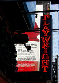 """Photo of a neon sign lit up in red letters that spell """"Playwright"""""""