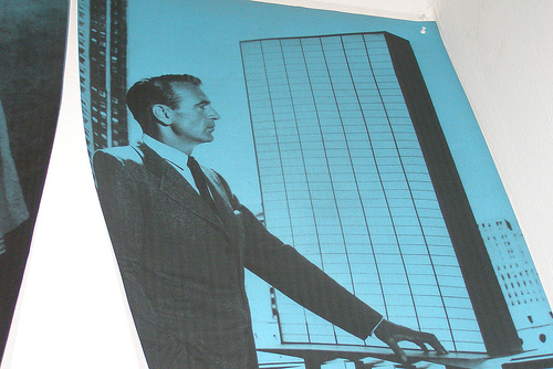 photo of a serious man in a suit looking at the picture of a tall building