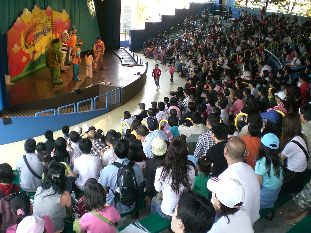 A photograph of an audience at a stage show featuring actors dressed as cartoonish animals.