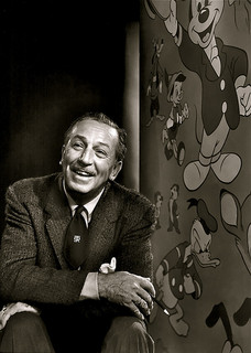 A photograph of animation pioneer Walt Disney. He is seated next to a mural depicting some of his more famous characters: Daffy Duck and Mickey Mouse.
