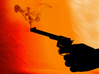 A silhouette photograph of a hand holding a smoking pistol