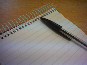 A pen laying on a on a blank sheet of paper in a spiral notebook