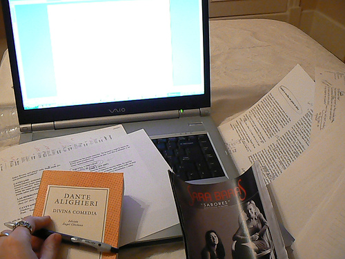 A photograph of a desk with an open laptop computer, written notes and several books on it. There is a female hand holding a pen visible.