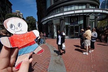 A photograph of a 'Flat Stanley' outside of a GAP store in an outdoor shopping area.