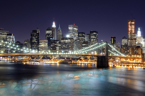 A photograph of downtown New York City (Manhattan) at night taken from the opposite side of the Manhattan bridge.