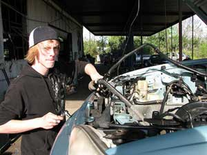 A photograph of a young man working on a car engine in a garage
