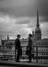 A photograph of two men standing on a bridge having a conversation. There is a cathedral in the background.