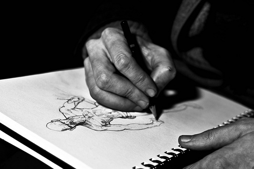 A photograph of a person's hand sketching out a comic book style character
