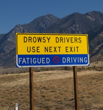 A photograph of a highway sign informing drowsy drivers to use the next exit