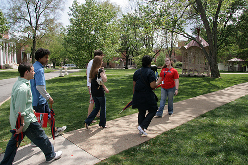 A young woman gives a tour of a college campus to a group of prospective students. She's walking backward to face them as they walk down a sidewalk together.