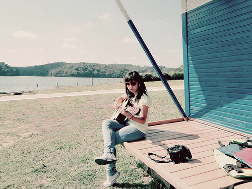 Sitting on the back porch and playing a guitar. A young woman wearing heart-shaped glasses plays, in the background a wide field, forests in the distance. The image is serene and quiet.