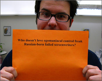 """A man holding a sign that reads """"Who doesn't love egomaniacal control freak Russian-born failed screenwriters?"""""""