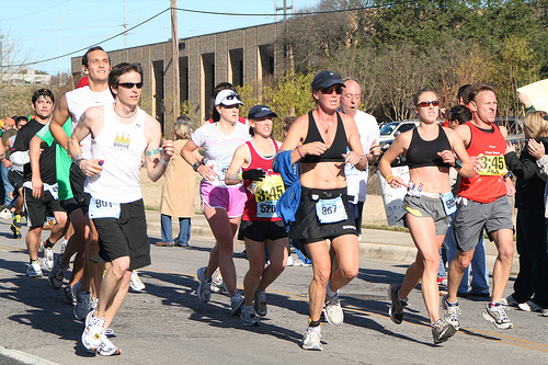 A photograph of men and women running in a road race. They are wearing typical runner's gear and paper number plates.