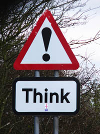 A photograph of a street sign that says Think!
