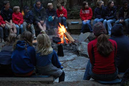 A photograph of a campfire in the evening with older and younger boys and girls sitting around it