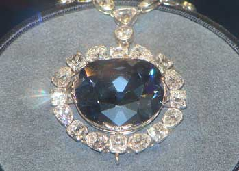 A photograph of the Hope Diamond. It is in a display case. The diamond itself is mounted as a pendant and surrounded by other diamonds on a necklace.