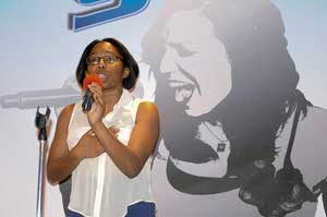 A photograph of a woman singing into a microphone at an audition.