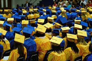 A photograph of a high school graduating class seated in an auditorium. They are all wearing traditional graduation apparel.