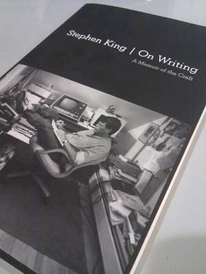 "A photograph of the book ""On Writing"" by Stephen King. The cover shows Stephen King working in his studio."