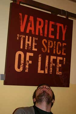 """A photograph of a man looking up at a sign that reads """"Variety is the Spice of Life."""""""