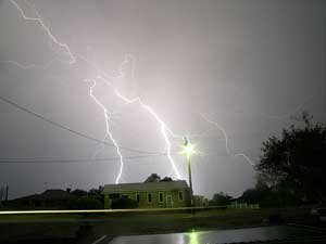 A photograph of lightning bolts striking near a house during a storm.