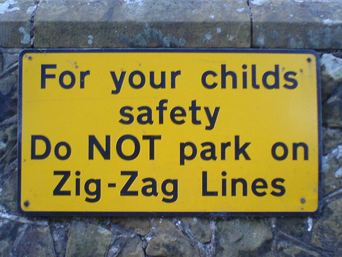 """photo a yellow that sign that reads """"For your child's safety Do NOT park on Zig-Zag Lines""""; capitalization is very inconsistent."""
