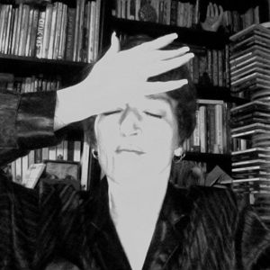 black and white photo of a woman bumping her hand against her forehead as though she forgot something