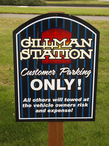 "photo of a sign that reads ""Gillman Station, Customer Parking ONLY! All others will towed at the vehicle owners risk and expense!"""