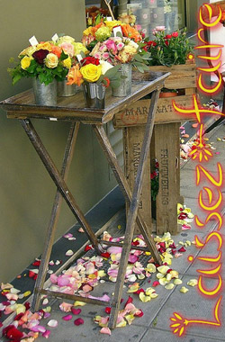 A sidewalk flower sale in front of a florist's shop. Petals are scattered around the ground in a carefree manner.
