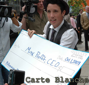 """Man at a protest, holding a blank check made out to """"Max Proffit, CEO, for Billionaire Bailout."""""""