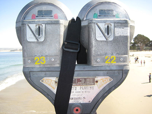 A photograph of a pair of parking meters on a beach